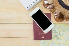 Preparación para el concepto que viaja, pasaporte, smartphone, gafas de sol, libro conocido, mapa en un fondo de madera Imagenes de archivo
