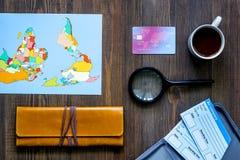Preparación para el viaje Mapa del mundo, tarjeta de banco y boletos en la opinión superior del fondo de madera de la tabla Imágenes de archivo libres de regalías