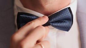 Preparación para la celebración de la boda El novio ajusta la corbata de lazo Primer almacen de video