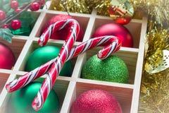 Preparación para la Navidad: bolas y bastón de caramelo festivos en la caja de madera, marco blanco ligero Imágenes de archivo libres de regalías