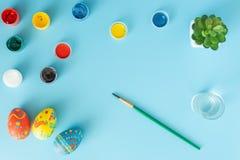Preparaci?n para las pinturas multicoloras de Pascua y los huevos coloreados hechos a mano al lado del cepillo en un concepto azu foto de archivo