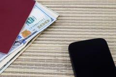 Preparación para las vacaciones, pasaporte con el dinero para el resto en la tabla y un teléfono celular de la manera Imágenes de archivo libres de regalías