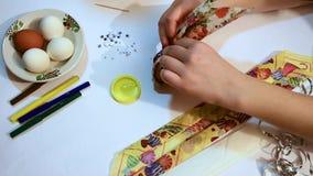 Preparación para Pascua Decoración para el día de fiesta Las manos femeninas con la manicura hermosa envuelven un huevo con los o