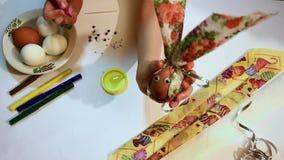 Preparación para Pascua Decoración para el día de fiesta El niño pintó una boca en un huevo con sus ojos y demostraciones él en e