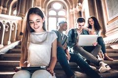 Preparación por un futuro brillante con sus amigos Un estudiante joven hermoso que se sienta en las escaleras en campus usando la fotos de archivo