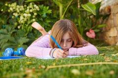 Preparación rubia de la muchacha del niño que miente en césped de la hierba imagen de archivo