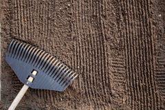 Preparaci?n de la tierra antes de plantar La textura del suelo con los surcos verticales del rastrillo, alista para plantar fotos de archivo