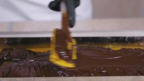 Preparaci?n del relleno para los dulces Chocolate líquido en la mermelada del albaricoque metrajes