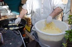 Preparacion frió los anillos de espuma de los buñuelos en mercado Foto de archivo