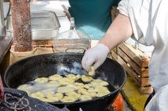 Preparacion frió los anillos de espuma de los buñuelos en mercado Imagen de archivo