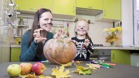 Preparaciones de Halloween La mamá y la hija están jugando en maquillaje Muestran gestos de la intimidación metrajes
