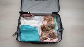 Preparaciones del viaje en la tabla de madera Mujer que pone la ropa en maleta almacen de video