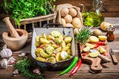 Preparaciones para las patatas que cuecen con ajo y hebrs Fotos de archivo libres de regalías