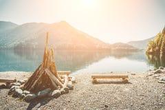 Preparado para encender una hoguera grande y bancos del abre una sesión la orilla de un lago hermoso con agua clara rodeada por e imagen de archivo