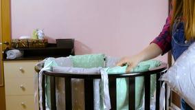 Preparan a una mujer embarazada con objeto de un ni?o reci?n nacido para la reuni?n Los muebles de madera de los ni?os plegables almacen de video