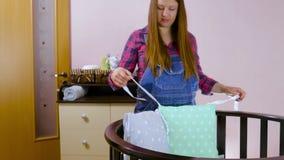 Preparan a una mujer embarazada con objeto de un ni?o reci?n nacido para la reuni?n Los muebles de madera de los ni?os plegables metrajes