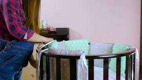 Preparan a una mujer embarazada con objeto de un ni?o reci?n nacido para la reuni?n Los muebles de madera de los ni?os plegables almacen de metraje de vídeo