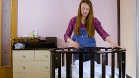 Preparan a una mujer embarazada joven con objeto de un ni?o reci?n nacido para la reuni?n Niños plegables de madera metrajes