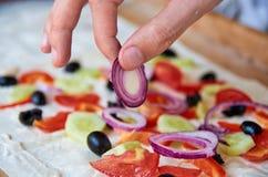 Preparando burrito vegetariano con le verdure, le olive e la cipolla vicine su su fondo di legno Mano con la fine della cipolla p Fotografia Stock Libera da Diritti