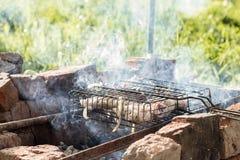 Preparando a carne em uma grelha de aço para a grade Fumo dos carvões fotos de stock