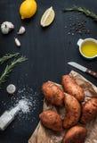 Preparando el romero asó las patatas dulces con aceite de oliva, el limón, la sal, la pimienta y el ajo Fotografía de archivo libre de regalías