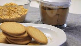 Preparando i bisuits per la cottura del dolce della crema del formaggio con i mirtilli archivi video