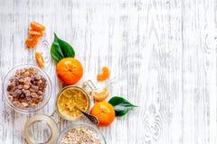 Preparando il porridge sano della prima colazione con le arance sul piano d'appoggio di legno leggero osservi il copyspace Fotografie Stock