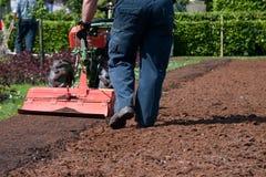 Preparando il terreno per la semina usando un mini trac Fotografia Stock Libera da Diritti