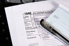 Preparando le tasse - assegno e moduli sulla tastiera Fotografia Stock Libera da Diritti