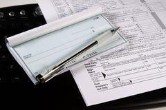 Preparando le tasse - assegno e moduli sulla tastiera Fotografie Stock Libere da Diritti