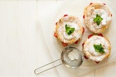 Preparando los anillos hechos en casa de los pasteles de los choux con crema y fresas del requesón adornó las hojas de menta Imágenes de archivo libres de regalías