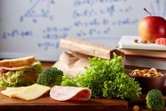 Preparando los bocadillos de jamón para la caja del almuerzo de la escuela en fondo de madera, cierre para arriba Fotografía de archivo