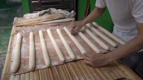 Preparando a massa para o baguette de cozimento na padaria filme
