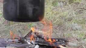Preparando o alimento na fogueira no acampamento selvagem filme
