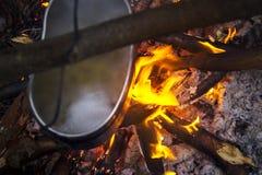 Preparando o alimento na fogueira no acampamento selvagem imagens de stock