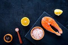 Preparando o bife salmon A parte de peixes vermelhos na placa de corte perto do sal do mar, pimenta, fatias do limão no fundo pre Foto de Stock