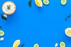 Preparando o molho grego do iogurte do pepino Role com o iogurte perto das hortaliças, pepino, laranjas, alho na mesa azul da coz Foto de Stock Royalty Free