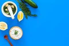 Preparando o molho grego do iogurte do pepino Role com o iogurte perto das hortaliças, pepino, laranjas, alho na mesa azul da coz Fotos de Stock Royalty Free