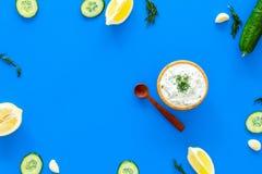 Preparando o molho grego do iogurte do pepino Role com o iogurte perto das hortaliças, pepino, laranjas, alho na mesa azul da coz Imagem de Stock