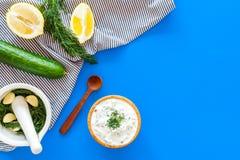 Preparando o molho grego do iogurte do pepino Role com o iogurte perto das hortaliças, pepino, laranjas, alho na mesa azul da coz Fotografia de Stock