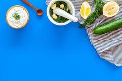 Preparando o molho grego do iogurte do pepino Role com o iogurte perto das hortaliças, pepino, laranjas, alho na mesa azul da coz Foto de Stock