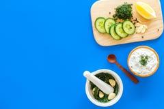 Preparando o molho grego do iogurte do pepino Role com o iogurte perto das hortaliças, pepino, laranjas na placa de corte no azul Foto de Stock Royalty Free