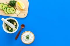Preparando o molho grego do iogurte do pepino Role com o iogurte perto das hortaliças, pepino, laranjas na placa de corte no azul Fotos de Stock Royalty Free