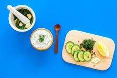 Preparando o molho grego do iogurte do pepino Role com o iogurte perto das hortaliças, pepino, laranjas na placa de corte no azul Imagens de Stock Royalty Free