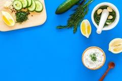 Preparando o molho grego do iogurte do pepino Role com o iogurte perto das hortaliças, pepino, laranjas na placa de corte no azul Fotos de Stock