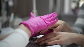 Preparando o prego ao tratamento de m?os O mestre usa o pulverizador especial para pregos do cliente no salão de beleza Close-up  video estoque