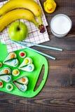 Preparando pasto veloce per lo scolaro Panini divertenti, latte, frutti sul copyspace di legno scuro di vista superiore del fondo Fotografia Stock