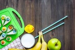 Preparando pasto veloce per lo scolaro Panini divertenti, latte, frutti sul copyspace di legno scuro di vista superiore del fondo Fotografie Stock
