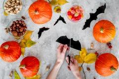 Preparando per Halloween Pipistrelli del taglio delle mani da carta Figure e zucche sulla vista superiore del fondo grigio Fotografie Stock Libere da Diritti