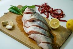 Preparando per il vapore della spigola con il limone, l'aglio ed il peperoncino rosso Fotografia Stock